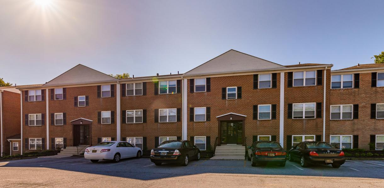outside view of one of the Melrose Place & Possum Park apartment buildings with cars in the lot and the sun shining
