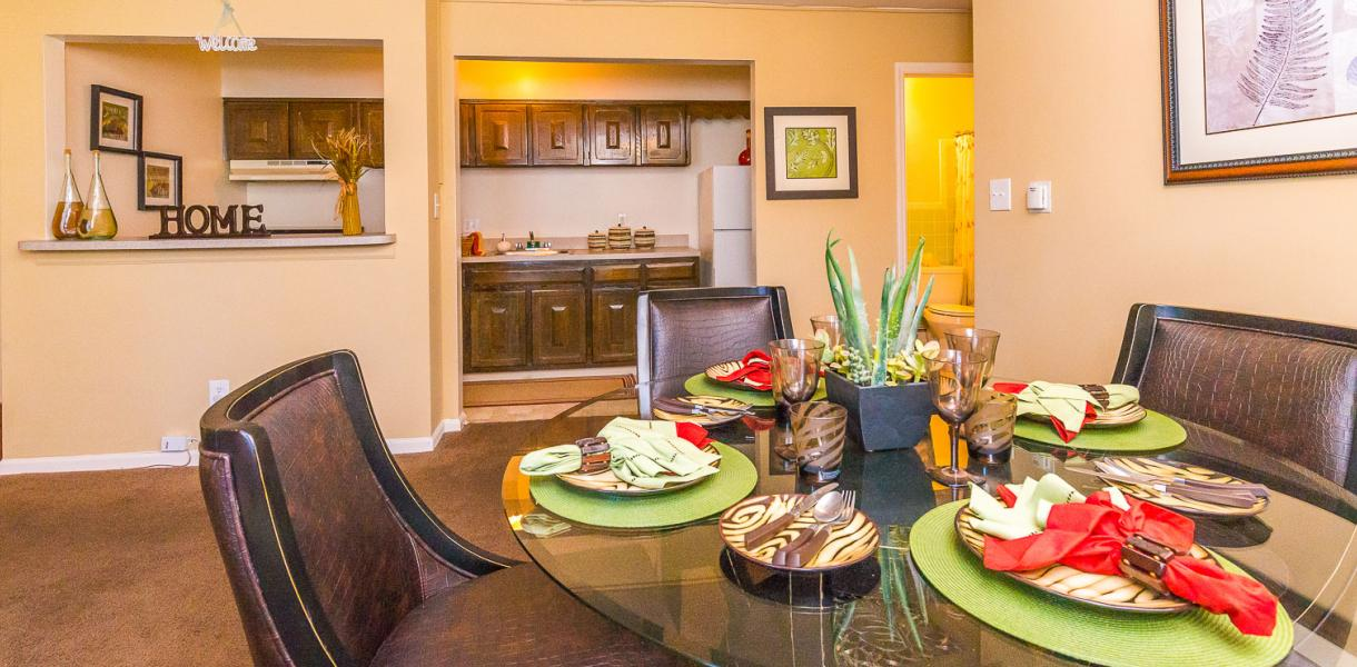 a living/dining area within one of the Melrose Place & Possum Park apartments with the kitchen in the background